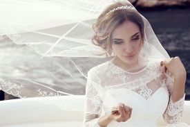 image of yacht  - fashion photo of beautiful sensual bride with dark hair in luxurious lace wedding dress posing on yacht - JPG