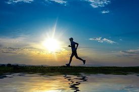 image of sprinters  - Silhouette man running on meadow over river sunrise  - JPG