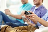 friendship, technology, games and home concept - close up of male friends playing video games at hom poster