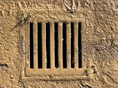 Water drain grate cover covered in mud after flood poster
