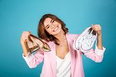 Portrait of a joyful woman dressed in pink suit holding pair of high heels shoes and pair of sneaker poster