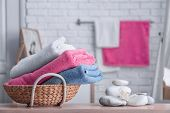 Basket with clean towels on table poster