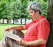 Middle-aged Woman Reading Book By Tree