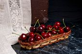 Several Red Sweet Cherries And Big Green Leaf On The Table. Fresh Organic Cherry In Yellow Wooden Ba poster