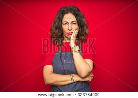 poster of Middle age senior woman wearing apron uniform over red isolated background thinking looking tired an