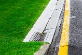 Drainage System Edge Tray With Concrete Grate For Rainwater Drainage Into The Sewer On A Road Side A poster