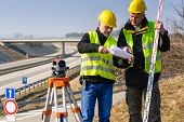 picture of theodolite  - Land surveyors on highway reading geodesist plans use tacheometer - JPG