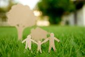 stock photo of environment-friendly  - Paper cut of family with house and tree on fresh spring green grass - JPG