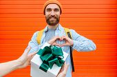 Unrecognizable Person Making Surprise Giving Gift Box To Amazed Beard Man Making Heart With Fingers, poster