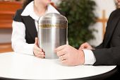 stock photo of urn funeral  - mortician with client comforting and advising - JPG
