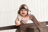 Cute Baby Pilot In The Helmet Sitting In The Wooden Brown  Airplane poster