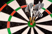 stock photo of fletching  - three darts in the bullseye - JPG