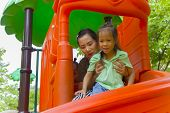 Mom And Daughter  Playing On Play Ground Play Slider Seesaw,  Funny Asian Family In A Park poster