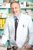 Mature pharmacist in his store smiling