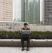Businessman in urban scene looking in briefcase