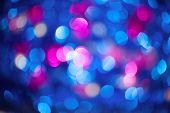 Multicolored christmas defocused lights on blue background. poster
