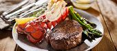 tasty surf & turf steak and lobster meal with asparagus on dinner plate poster