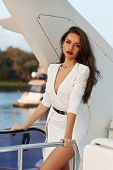 Young Elegant Stunning Woman In White Luxury Dress Standing And Posing At Expensive Motor Yacht On A poster