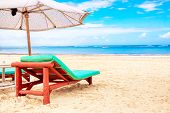 A Sun Lounger Under An Umbrella On The Sandy Beach By The Ocean And Cloudy Sky. Vacation Background. poster