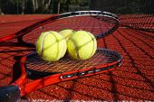 Tennis Scene With Black Net Shadow, Tennis Balls Resting On Top Of A Tennis Racquet On Red Hard Cour poster