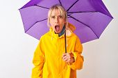 Middle age woman wearing rain coat and purple umbrella over isolated white background scared in shoc poster