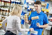 stock photo of cashiers  - Assistant seller help buyer by demonstrating paint roller for painting at hardware store - JPG