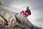 stock photo of ascending  - young businessman with red car climbs the rocks - JPG