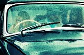 stock photo of wiper  - Young people driving retro car in the rain - JPG