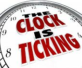 image of stimulating  - A white clock with the words The Clock is Ticking to symbolize an impending deadline or end to an event or period - JPG