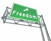 A green freeway sign with the word Freedom and an arrow pointing the way to a path of independence,
