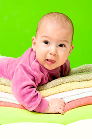 picture of fussy  - Fussy baby on the towels on green background - JPG