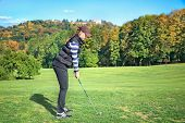 stock photo of ladies golf  - Young woman on a golf course on a sunny autumn day in the background of the old castle - JPG