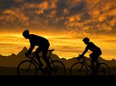 picture of exercise bike  - silhouette of the cyclists riding a road bike at sunset  - JPG