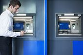 Young businessman taking out money from ATM
