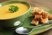 stock photo of butternut  - Vegetables soup with bread and spoon on a wooden table - JPG
