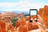 Smartphone camera phone taking photo picture of Bryce Canyon nature. Closeup of mobile phone camera