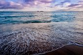 stock photo of waikiki  - Waves break on famous Waikiki beach in Oahu at sunset - JPG