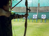 foto of longbow  - Archer man pulls the bowstring and arrow aiming at a target - JPG
