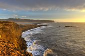 stock photo of promontory  - The black sand beach of Reynisfjara and the mount Reynisfjall from the Dyrholaey promontory in the southern coast of Iceland - JPG