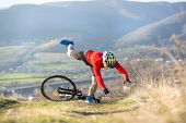 image of biker  - Mountain Biker has a painful looking crash with his bike - JPG