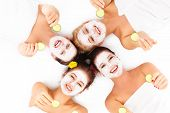 stock photo of facials  - A picture of four friends enjoying their time in spa with facial masks over white background - JPG