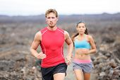 Running sport people jogging on trail in cross country run outdoors training for marathon or triathl