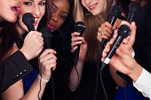 stock photo of singing  - Portrait of happy multiethnic friends singing into microphones at karaoke party - JPG