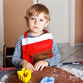 foto of ginger bread  - Adorable boy baking ginger bread cookies for Christmas in home - JPG