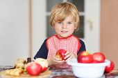 picture of pie-in-face  - Adorable little child helping and baking apple pie in home - JPG