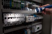stock photo of fuse-box  - Cropped image of male technician analyzing fusebox with flashlight - JPG