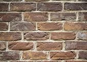 stock photo of slash  - Rectangular brown brick wall with cracks and slashes.