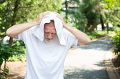 picture of pain-tree  - Closeup portrait old gentleman in white shirt having difficulties with extreme heat high temperatures very tired holding towel over head as shade isolated green trees paved road background - JPG