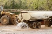 image of tank truck  - large truck pulling a water tank spraying for dust control at a log yard at a lumber processing mill that specializes in small logs - JPG