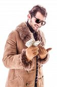 picture of hustler  - a young man wearing a sheepskin coat isolated over a white background holding banknotes - JPG
